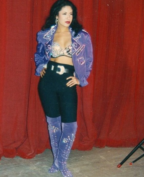 Selena Quintanilla wearing black leggings with purple boots, rhinestone bustie and purple jacket
