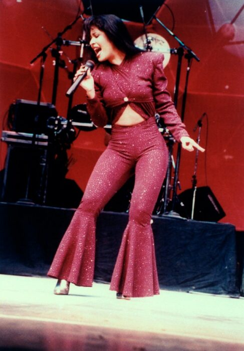 Selena Quintanilla wearing a cherry colored jump suit with glitter details