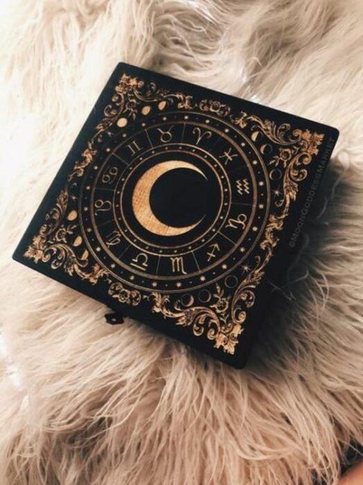 Artículo decorativo inspirado en la Luna de una caja de madera oscura con una Luna y los signos del zodiaco a su alrededor en color dorado