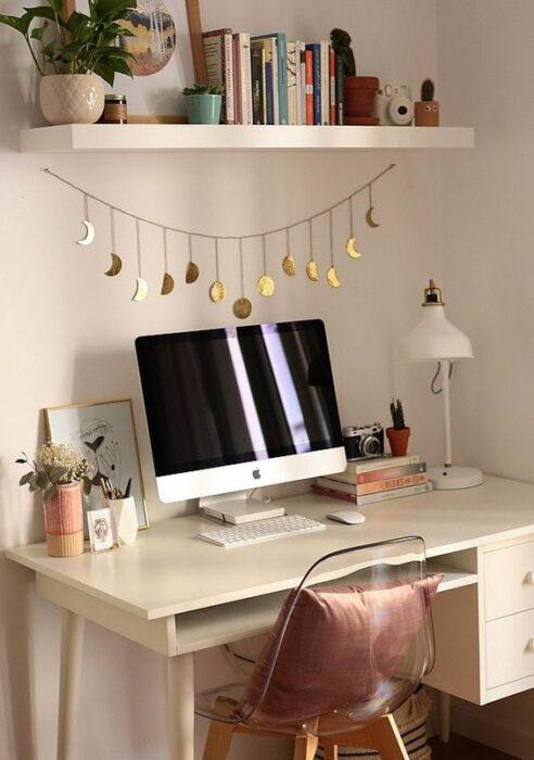 Área de trabajo con un colgante dorado de la Luna sobre la pared donde se encuentra el escritorio