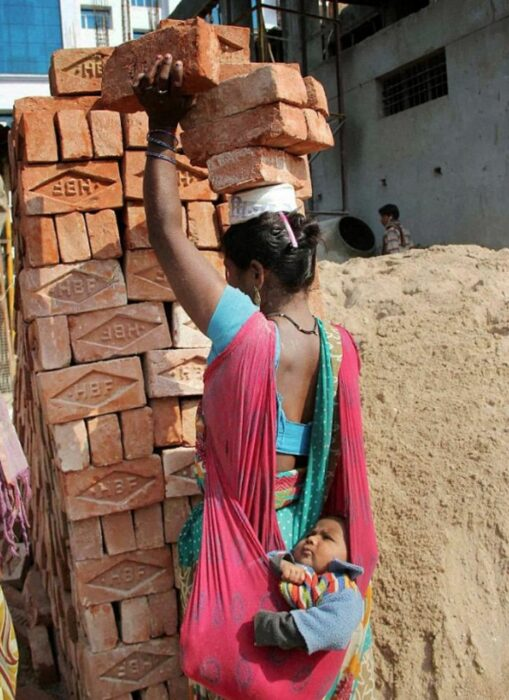 Madre trabaja cargando ladrillos en su cabeza y cuida a su hijo al mismo tiempo
