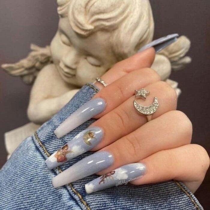 Manicura de acrílico estilo aesthetic de color azul, con diseño a mano alzada de angelitos y cielo
