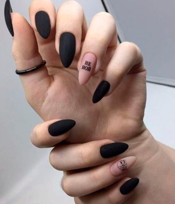 Halloween-inspired manicure in black with one in nude with black details