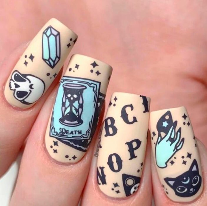 Halloween inspired manicure with beige background with black and sky blue details