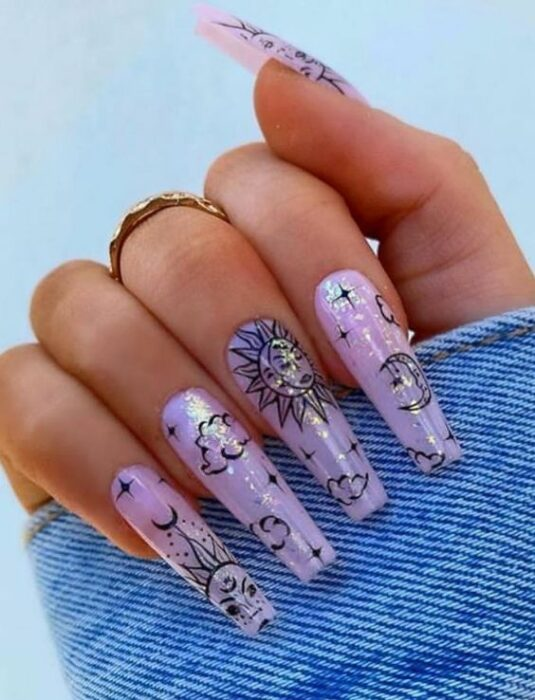 Aesthetic style acrylic manicure with lilac background with black design of suns, clouds and stars