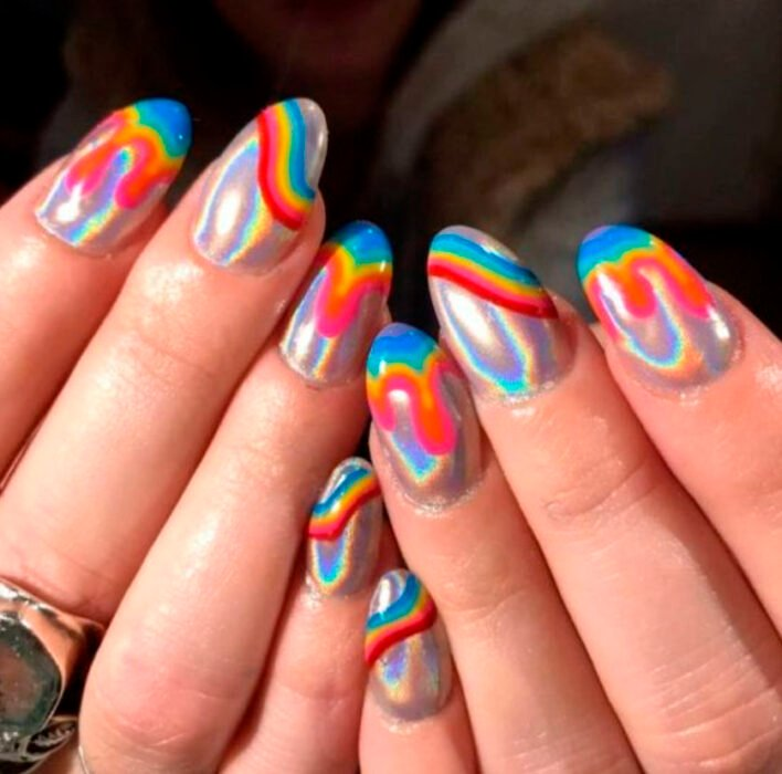 Aesthetic style acrylic manicure in iridescent silver color, with blue, yellow and red lines
