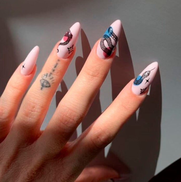 Baby pink background aesthetic style acrylic manicure with freehand snake design along all nails