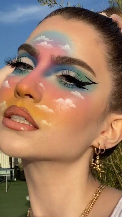 Maquillaje aesthetic en tonos arcoíris y nubes en el rostro