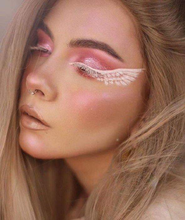 Aesthetic makeup in pink and white tones with angel wings in the eyes