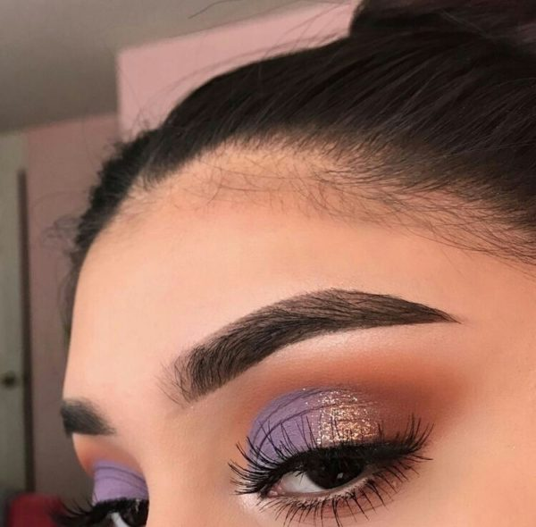 Girl with makeup in shiny purple and gold tones