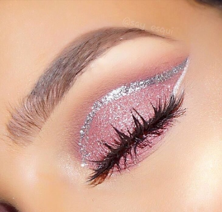 Girl with a pink eye makeup with a silver eyeliner