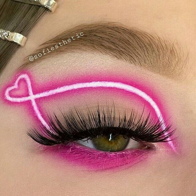 Girl with an eye makeup in pink tones with neon effect
