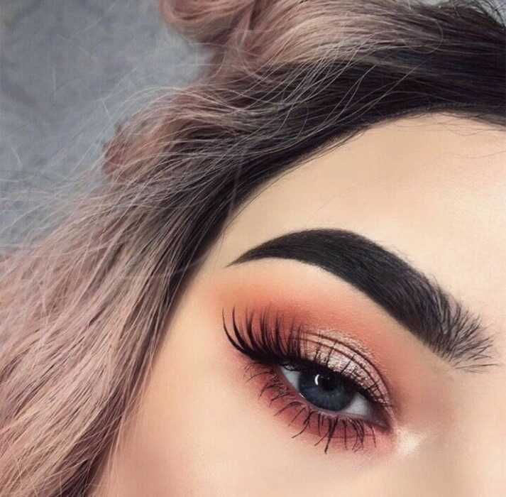 Girl with an eye makeup in warm colors of gold with pink