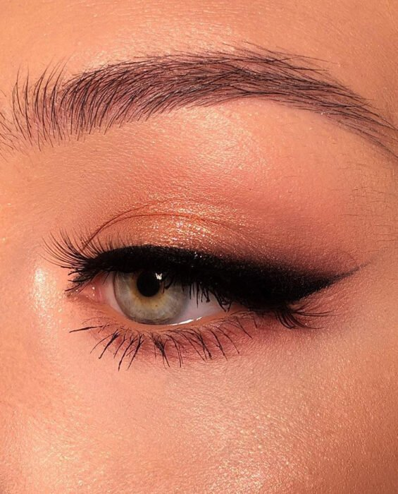 Girl with a gold eye makeup with a big black cat eye