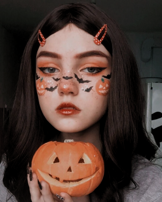 Girl with makeup in orange colors inspired by Halloween