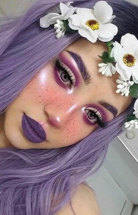 Chica con maquillaje para Halloween en colores morados con flores en la cabeza