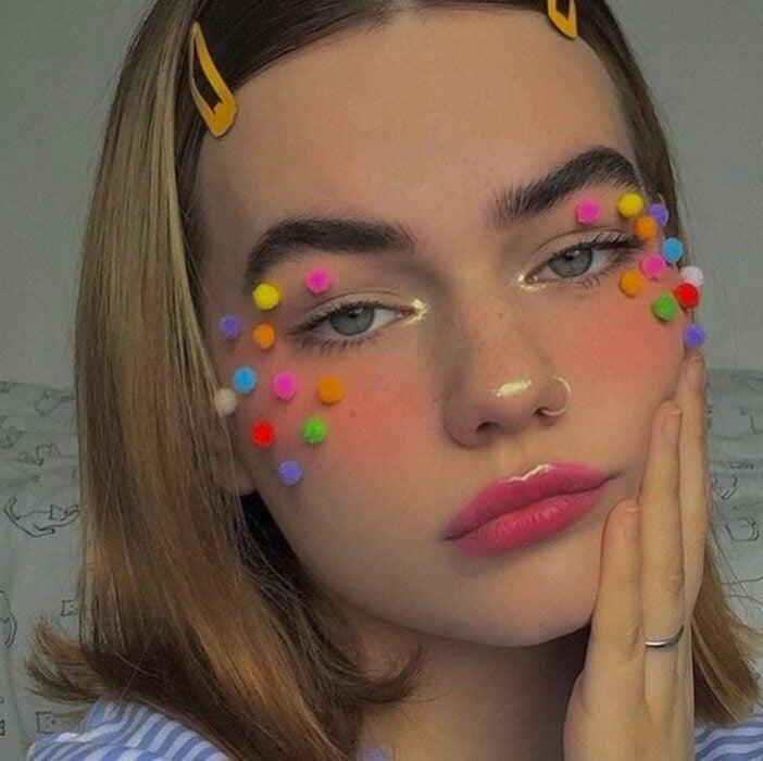 Chica con maquillaje en naranja y pequeños pompones