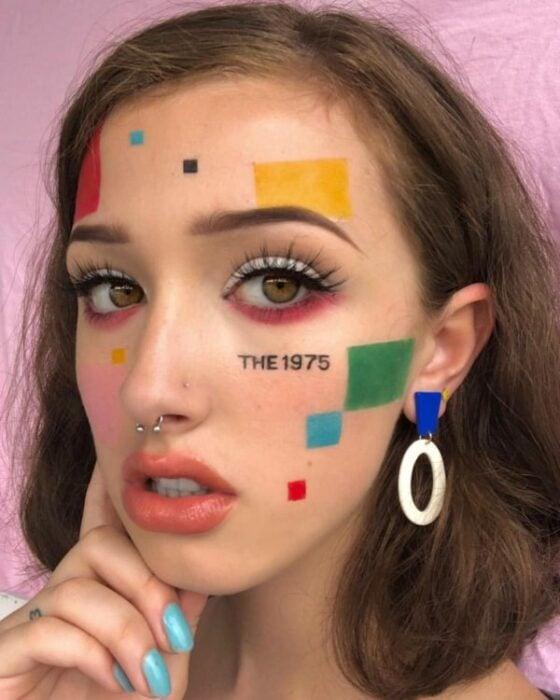Chica con maquillaje a cuadros de colores en el rostro