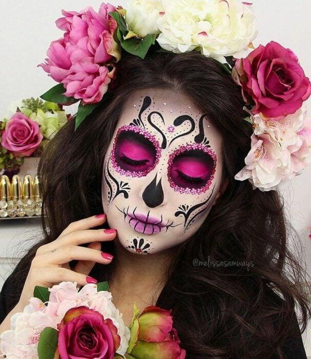 Chica con un maquillaje de catrina en colores rosas con blancos