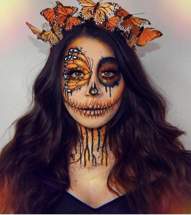 Girl with a catrina makeup in yellow colors with butterflies
