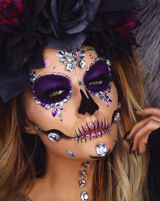 Girl with a catrina makeup in purple colors with pearls and rhinestones