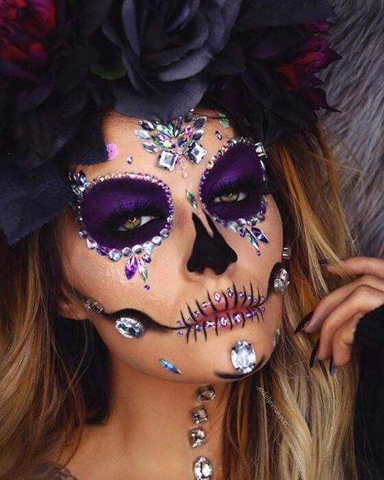Chica con un maquillaje de catrina en colores morados con perlas y pedrería