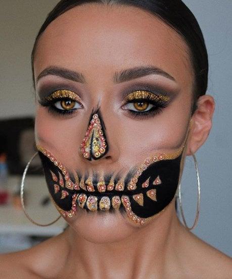 Chica con un maquillaje de catrina en colores negros con dorado