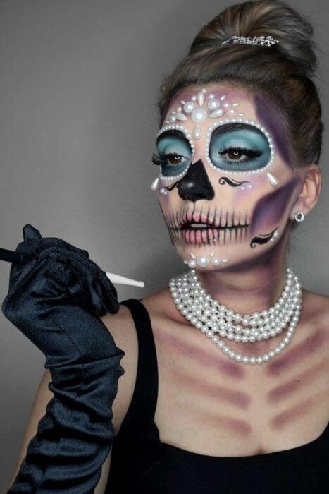 Chica con un maquillaje de catrina en colores azules con perlas