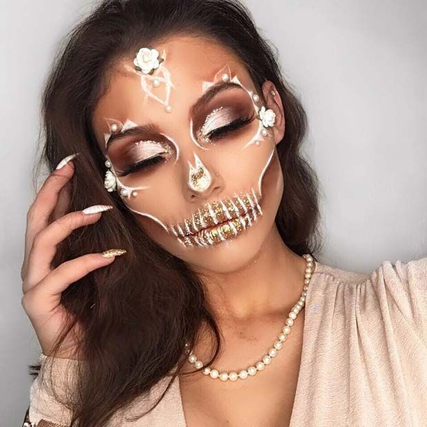 Girl with a catrina makeup in gold colors