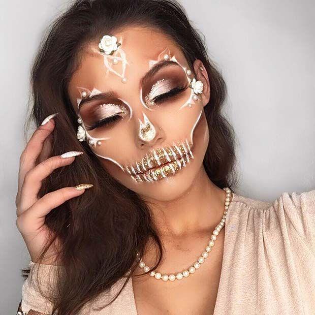 Chica con un maquillaje de catrina en colores en dorados