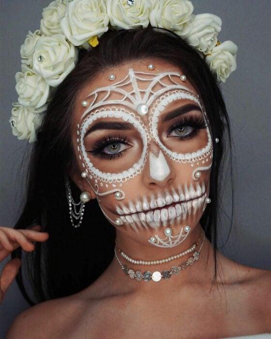 Chica con un maquillaje de catrina en colores blancos