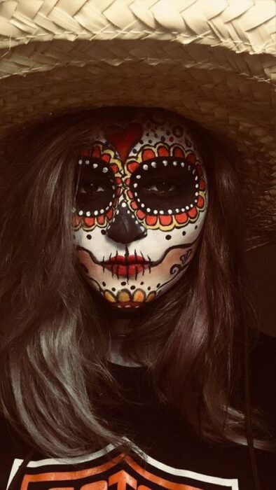 Chica con un maquillaje de catrina en colores naranja con blanco