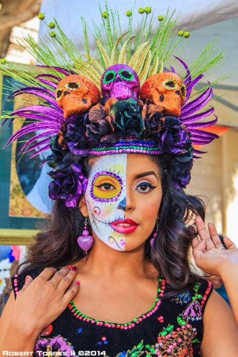 Chica con un maquillaje de catrina en colores blancos con amarillo y morada
