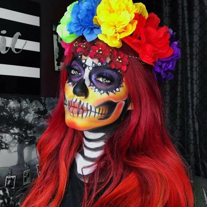 Chica con un maquillaje de catrina en colores rojos con morado y amarillo