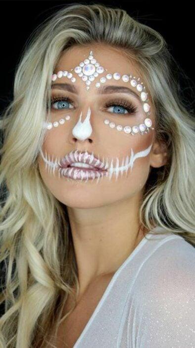 Chica con un maquillaje de catrina en colores blancos con perlas