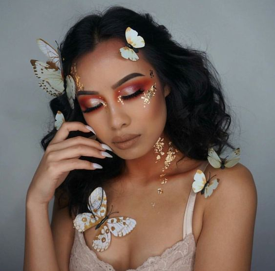 Chica con maquillaje casual y mariposas pegadas en el rostro