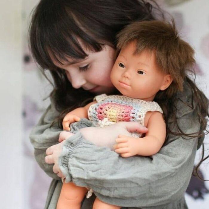 Niña jugando con muñeca Miniland, de la colección de síndrome de Down
