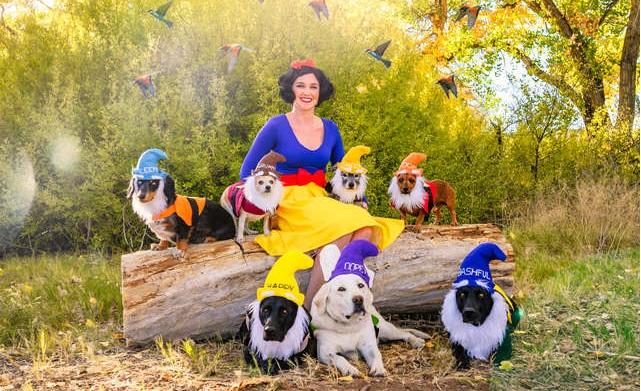 Mujer disfrazada de Blancanieves junto a sus siete perros