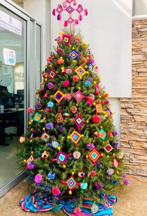 Decoración de Navidad con temática mexicana; árbol navideño con artesanías, ojo de Dios, arte huichol,