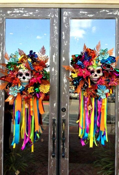 Decoración de Navidad con temática mexicana; coronas para la puerta con calaveras flores, listones de colores azul, verde, amarillo, anaranjado, rosa, azul y morado