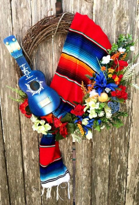 Decoración de Navidad con temática mexicana; corona para la puerta con ramas, reboso de colores rojo, azul y anaranjado, guitarra pequeña y flores de plástico