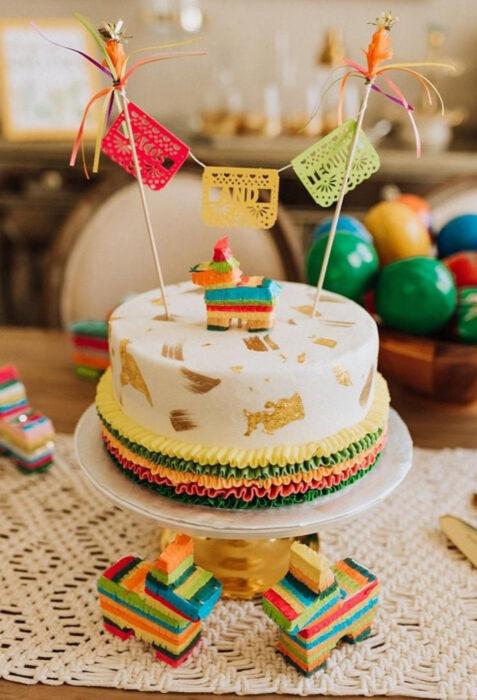 Decoración de Navidad con temática mexicana; pastel temático en la mesa, con papel picado, piñata de caballo de colores rojo, amarillo, verde, azul y rosa