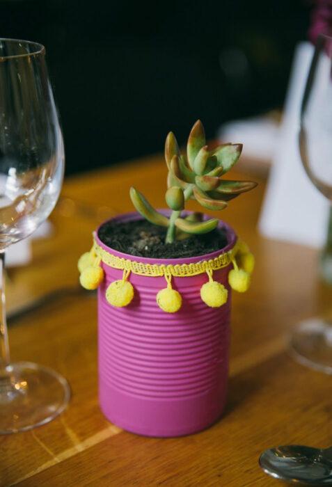Decoración de Navidad con temática mexicana; centro de mesa de maceta de lata de comida, color rosa con adornos amarillos, suculenta