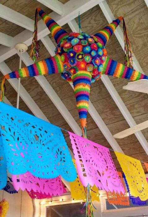 Decoración de Navidad con temática mexicana; piñata de estrella de colores anaranjado, azul, rojo, verde, amarillo y papel picado