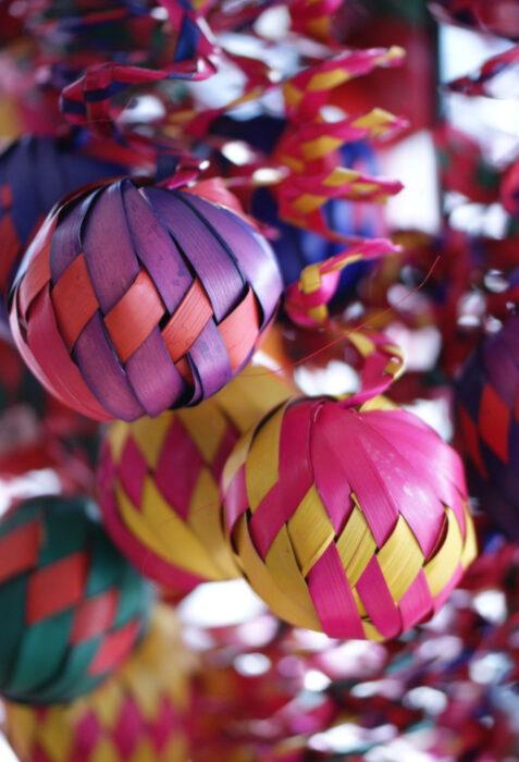 Decoración de Navidad con temática mexicana; esferas de hoja de palma de colores morado, anaranjado, rosa y amarillo, árbol navideño