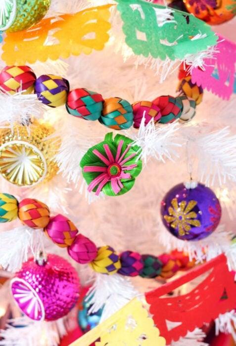 Decoración de Navidad con temática mexicana; árbol navideño blanco con adornos coloridos de México, guirnaldas y flores de hoja de palma, amarillo, rojo, morado, verde, azul, rosa, esferas, papel picado