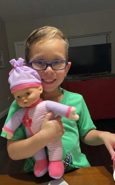 Niño sentado en el asiento de un coche sosteniendo una muñeca que pidió de regalo