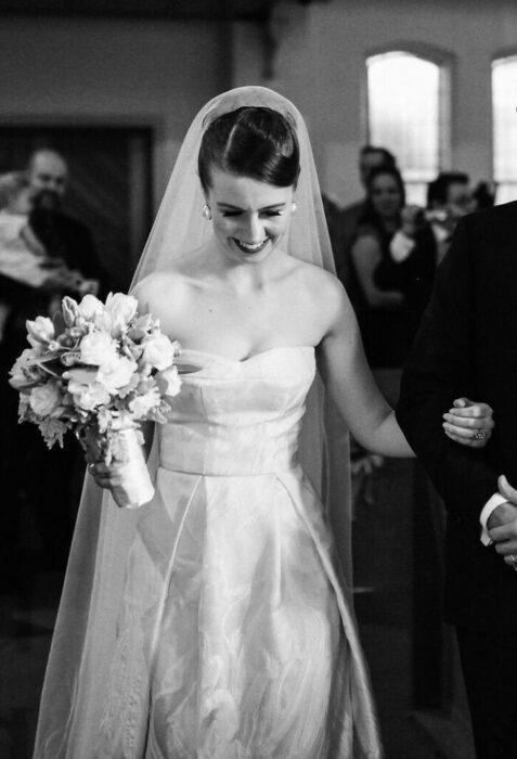 Fotografía blanco y negro de novia caminando al altar con vestido de novia strapless