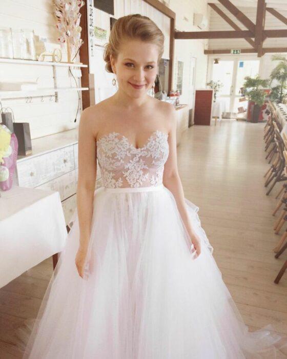 Novia rubia con vestido con la parte superior de encaje y transparencia y la falda con material suave y con volumen