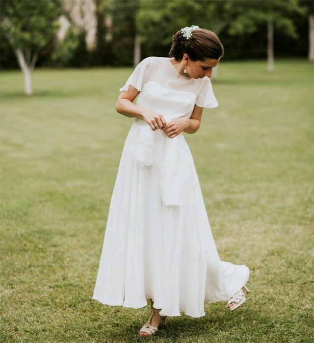 Novia en jardín con recogido elegante con peineta blanca con vestido hasta los tobillos con transparencia en la parte superior y sandalias beige de tacón